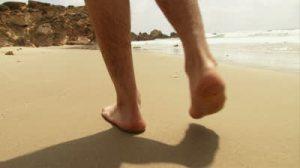 stock-footage-cu-guy-s-feet-walking-on-beach